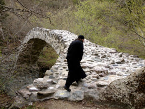 "Georgian monk walks across medieval Rkoni single-arch ""Tamar"" bridge near Rkoni Monastery, Georgia. Seen on John Graham Tours."