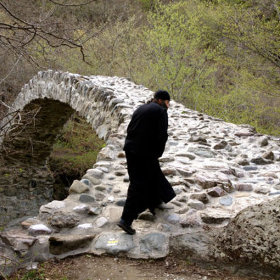 "Georgian monk walks across medieval Rkoni single-arch ""Tamar"" bridge near Rkoni Monastery, Georgia. Seen on John Graham Tours."